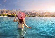 Woman at Issyk Kul Lake. Beautiful woman in red striped hat swimming in crystal clean Issyk Kul lake with mountains background at sunrise in Kyrgyzstan Royalty Free Stock Photos