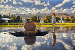 Woman at Issyk Kul Lake. Tourist woman in red Hat and striped dress walking down the hall with stone sphere in Ruh Ordo cultural complex at Issyk Kul lake with Royalty Free Stock Photos