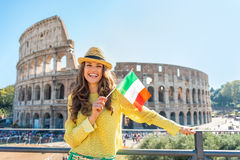 Woman with italian flag in front of colosseum. Portrait of happy young woman with italian flag in front of colosseum in rome, italy stock photos