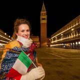Woman with Italian flag near St Marks Campanile, Venice. Classical tourist enjoyment in Venice, Italy.  smiling elegant tourist woman wrapped in a long scarf at Stock Photography