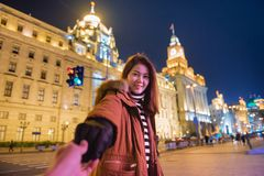 Woman in jacket clothes leading man to the bund in shanghai stock photography