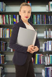 Woman in a jacket with a folder in hands. In a library Royalty Free Stock Photo