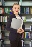 Woman in a jacket with a folder in hands. In a library Royalty Free Stock Images