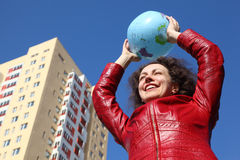 Woman in jacket holding balloon in form of globe Royalty Free Stock Photo