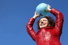 Woman in jacket holding balloon in form of globe Royalty Free Stock Images