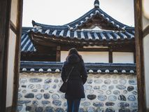 A woman in jacket opening the door in Namsangol Hanok Village on a fine weather stock images