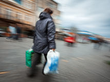 Woman in a jacket with shopping plastic bags Royalty Free Stock Photos