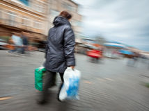 Woman in a jacket with shopping plastic bags Royalty Free Stock Photo