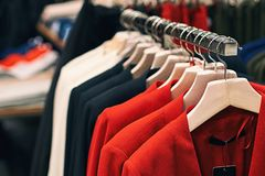 Woman jackets in red, blue, white and other colors on hangers in a retail clothes store. stock photography