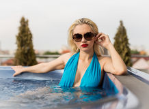Woman in jacuzzi. Beautiful blonde woman posing in jacuzzi royalty free stock image