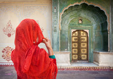 Woman in Jaipur city palace. Woman in red scarf looking at green gate door in City Palace of Jaipur, Rajasthan, India royalty free stock photos