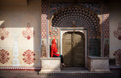 Woman in Jaipur city palace. Woman in red scarf sitting near Lotus gate in City Palace of Jaipur, Rajasthan, India Stock Photo