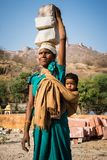 Woman from Jaipur, India. A woman is carrying stones on her head while wearing the child on the back. She works hard for a few extra money for her family in a Royalty Free Stock Photography