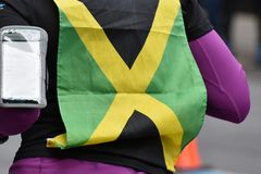 Woman with Jamaican flag on back. A runner with a Jamaican flag pinned to her back stock images