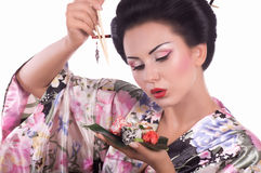 Woman in Japanese kimono with chopsticks and sushi roll Royalty Free Stock Photos