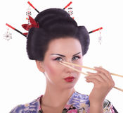 Woman in Japanese kimono with chopsticks and sushi roll Royalty Free Stock Images