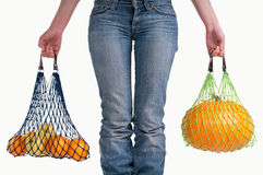 Woman with jeans carrying yellow fruits. Woman carrying shopping bags with yellow fresh fruits isolated on white background Royalty Free Stock Photos