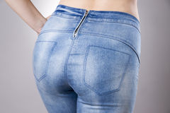 Woman in jeans close up. Beautiful female hips and buttocks. On a gray background Royalty Free Stock Images