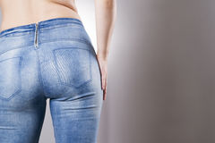 Woman in jeans close up. Beautiful female hips and buttocks. On a gray background Stock Image