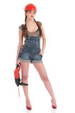 Woman in jeans coverall holding perforator drill. Young playful woman in jeans coverall and orange helmet holding perforator dril with huge auger Stock Photo