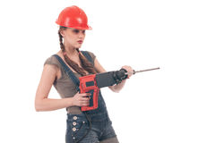 Woman in jeans coverall holding perforator drill. Young playful woman in jeans coverall and orange helmet holding perforator drill with huge auger Royalty Free Stock Image