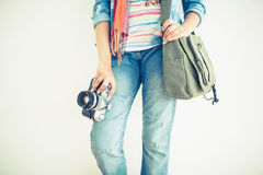 Woman in jeans holding camera and shoulder bag Royalty Free Stock Images