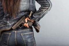Woman in jeans is holding a gun. In her hand Stock Photography
