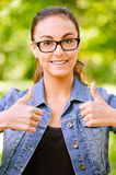 Woman in jeans jacket lifts thumbs Royalty Free Stock Photo