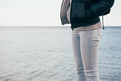 Woman in jeans and jacket standing on the sea background Royalty Free Stock Photo