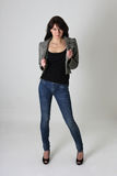 Woman in jeans and leather jacket over grey Stock Photo