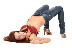 Woman in jeans lies on a white Stock Photography