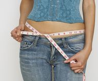 Woman in jeans measuring waist Royalty Free Stock Photography