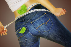 Woman in jeans measuring yourself tape and loses weight Stock Photos