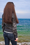 Woman in jeans on the sea coast. Royalty Free Stock Images