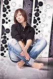 Woman in jeans and shirt sitting on floor against fancy wall Royalty Free Stock Images