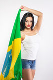 Woman in jeans short holding large brazil flag Stock Photo