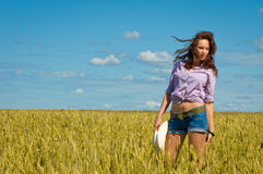 A woman in jeans shorts with cowboy hat in hand Stock Images