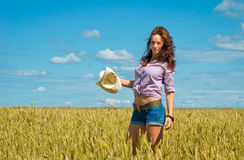 A woman in jeans shorts with cowboy hat in hand Royalty Free Stock Image
