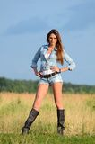 The woman in jeans shorts in the field Stock Image