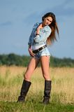 The woman in jeans shorts in the field Stock Photo