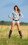 The woman in jeans shorts in the field. The woman in jeans shorts in field Stock Photo
