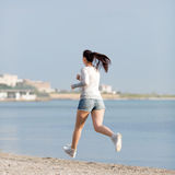 Woman in jeans shorts runs along seashore Stock Photography