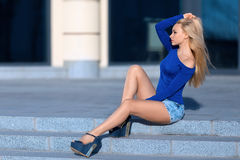 Woman in jeans shorts sitting outdoor. Beautiful blonde woman in blue jeans shorts costume and high heels sitting outdoor on the stone stairs Royalty Free Stock Images