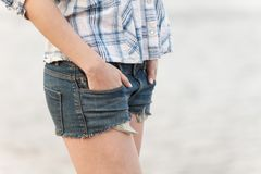 Woman in jeans shorts walking on sand. Stock Photo