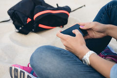 Woman in jeans sitting on the beach sand. Cross-legged and using a mobile phone with a touch screen. Next is the backpack. Close up Stock Photos