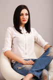 Woman in jeans sitting on chair Royalty Free Stock Photos