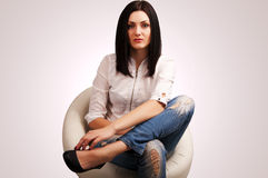 Woman in jeans sitting on chair Stock Images