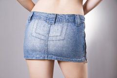 Woman in jeans skirt close up. Beautiful female hips and buttocks. On a gray background Royalty Free Stock Photos