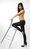 Woman in jeans with stool, side view stock image