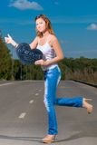 Woman in jeans and t-shirt   travels hitchhiking Stock Photos
